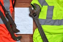 可调扳手和橙色和绿色信号工作者衬衣的纸谎言 静物画联合修理、铁路或者plu 库存图片
