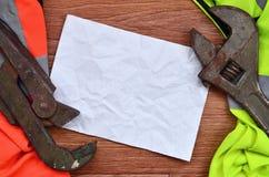 可调扳手和橙色和绿色信号工作者衬衣的纸谎言 静物画联合修理、铁路或者plu 免版税库存照片