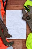 可调扳手和橙色和绿色信号工作者衬衣的纸谎言 静物画联合修理、铁路或者plu 库存照片
