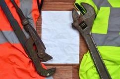可调扳手和橙色和绿色信号工作者衬衣的纸谎言 静物画联合修理、铁路或者plu 免版税库存图片