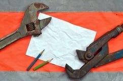 可调扳手和纸片与两支铅笔的 静物画联合修理、铁路或者配管工作 免版税库存照片