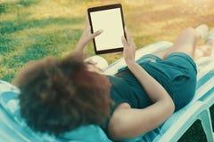 可躺式椅的女孩有digtial垫大模型的  免版税库存照片