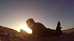 可移植的控制台 人在沙子和戏剧说谎在便携式的控制台在日落阳光生活方式 免版税库存照片