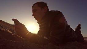 可移植的控制台 人在沙子和戏剧说谎在便携式的控制台在生活方式日落阳光 库存照片