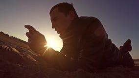 可移植的控制台 人在沙子和戏剧说谎在便携式的控制台在生活方式日落阳光 免版税库存照片