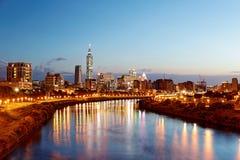 台北市与摩天大楼和在光滑的水的美好的反射夜视图由河沿的 库存图片
