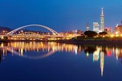 台北市夜风景有摩天大楼&桥梁的美好的反射的在水由河沿在黄昏 免版税图库摄影