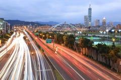 台北市夜风景,有Taipai的101在辛伊区,与曲拱桥梁的市中心和汽车在堤堰大道落后 图库摄影