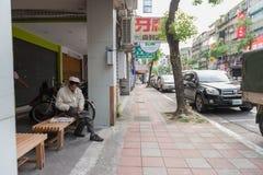 台北,台湾- 2016年11月30日:台北街在一个郊区中,区 人们坐长凳 免版税库存图片