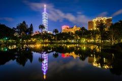 台北101和中山公园的一个湖在晚上,在信益中, Taip 库存图片
