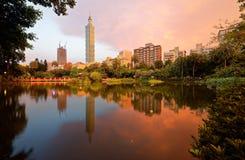 台北101塔湖边风景在摩天大楼中的在信义区街市在黄昏有反射看法在池塘的 免版税库存照片