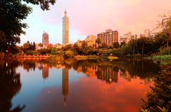 台北101塔湖边风景在摩天大楼中的在信义区街市在黄昏有反射看法在池塘的 库存图片