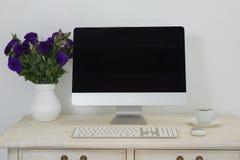 台式计算机、花瓶和咖啡在桌上 免版税库存图片