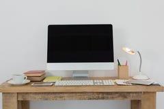 台式计算机和各种各样的办公室辅助部件在桌上 免版税库存照片