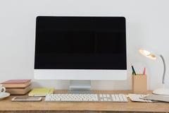 台式计算机和各种各样的办公室辅助部件在桌上 图库摄影