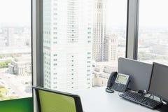 台式计算机和输送路线在书桌上打电话由玻璃窗在办公室 库存图片