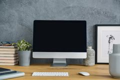 台式计算机大模型在木书桌上的有灰色wor的植物的 免版税库存图片