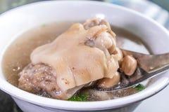 台湾` s特别著名快餐:花生猪肉knucklepig ` s在一个白色碗的小跑步马汤在石桌,台湾纤巧上 免版税库存照片