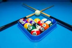 台球在三角的在桌上的水池球和棍子 库存照片