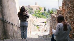 台阶的两年轻女人 他们中的一个画和其他照片风景 影视素材