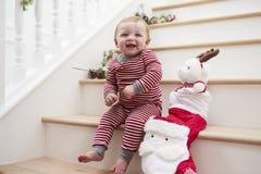 台阶的女孩在有玩具的睡衣在圣诞节 免版税库存图片