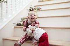台阶的女孩在有玩具的睡衣在圣诞节 库存照片