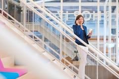 台阶的微笑的女实业家在有她的电话的现代办公室 图库摄影