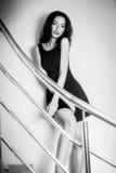 台阶的美丽的深色的妇女在黑色的一件黑礼服 库存照片