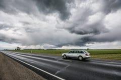 史诗天空,在路的快行汽车 免版税图库摄影