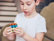 叶卡捷琳堡,俄罗斯- 2019年3月,01日 有Rubik的立方体的男孩在家 库存图片