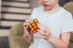 叶卡捷琳堡,俄罗斯- 2019年3月,01日 男孩庄稼画象有接近Rubik的立方体的在家  库存图片