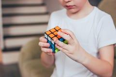 叶卡捷琳堡,俄罗斯- 2019年3月,01日 男孩庄稼画象有接近Rubik的立方体的在家  免版税库存图片