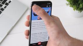 叶卡捷琳堡,俄罗斯- 2018年10月3日:使用在iPhone x智能手机的人CNN app,浏览通过页 影视素材