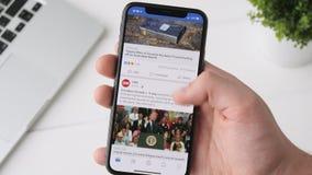 叶卡捷琳堡,俄罗斯- 2018年10月3日:使用在iPhone x智能手机的人Facebook app,浏览通过页 股票录像
