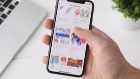 叶卡捷琳堡,俄罗斯- 2018年10月3日:使用在iPhone x智能手机的人Rakutten app,浏览通过页 股票视频