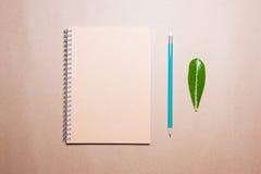 叶子、笔记本和铅笔在一张包装纸 在视图之上 免版税库存图片