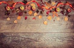 叶子、苹果和莓果的秋天安排在木背景与自由空间文本的 顶视图,概念  免版税图库摄影