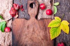 叶子和小苹果在空的切板附近在木土气背景 顶视图 框架 复制空间 感恩日 平面 免版税库存图片