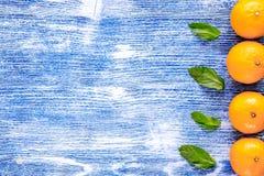 叶子和桔子在蓝色书桌背景顶视图空间文本的 免版税库存照片