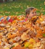 叶子堆的男孩 免版税库存图片