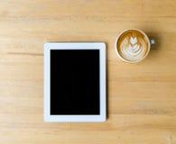 叶子拿铁艺术咖啡和桌 免版税库存图片
