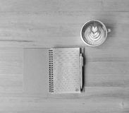 叶子拿铁艺术咖啡和笔记本有笔的 库存照片