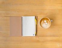 叶子拿铁艺术咖啡和笔记本有笔的 免版税图库摄影