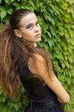 叶子的背景的美丽的女孩在街道上的秋天天有在一件黑礼服的幻想构成的 免版税图库摄影