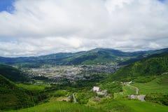 绿叶山风景与白色多云天空的全景和镇视图 库存图片