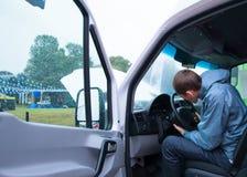 司机人检查在货物搬运车上的方向盘专栏 库存图片