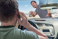 司机叫使用在汽车的智能手机击中步行者 库存照片