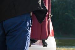 司机在与事的树干投入手提箱休息 免版税库存照片