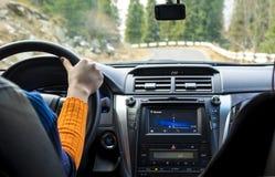 司机在方向盘的` s手在山路的一辆汽车里面 库存照片