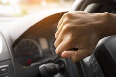 司机在方向盘的` s手在有美好的绿色森林透视的一辆汽车里面 库存图片